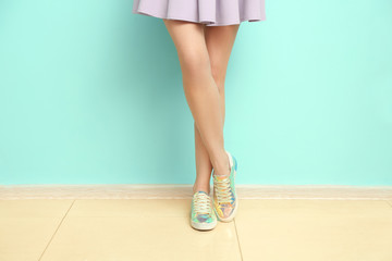 Young woman in stylish casual shoes near color wall