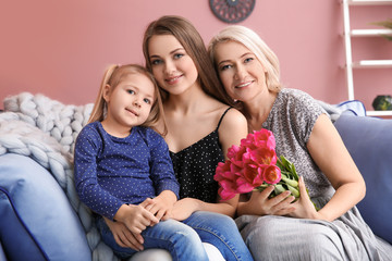 Happy young woman with her mother and daughter at home