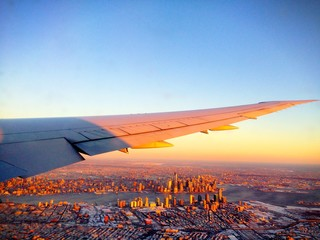 Scenic and impressive aerial view of the New York City Manhattan Skyline (USA) from an airplane during sunset / sunrise on a winter day