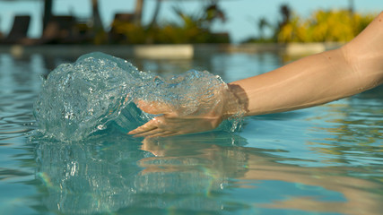 CLOSE UP: Playful female tourist drags her hand through water and creates a wave