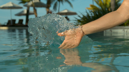 CLOSE UP: Woman drags her hand through calm pool water and creates a ripple.