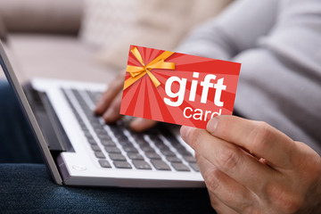 Person Working On Laptop Holding Gift Card