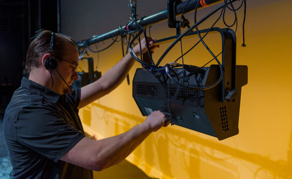 Male theater technician adjusting theatrical lighting units