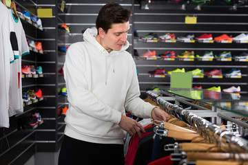 tennis male is choosing new shirt for play in time shopping in the store