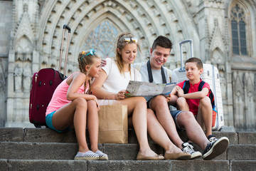 Smiling family with children sitting near cathedral with map