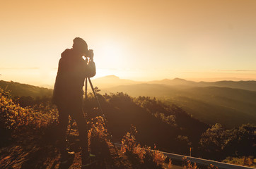 silhouette of photographer on top of mountain at sunrise background(vintage style)