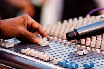 Sound engineer adjusting audio mixing console