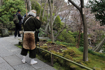 A traditional Japanese pilgrim (?) taking photos at Hasedera Temple