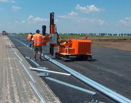 Road worker mounting the roadside guardrail