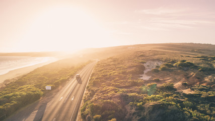 Aerial View of Car Driving Down Great Ocean Road, Australia at Sunset