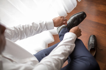 Man wears black shiny shoes in morning wedding preparations or business work