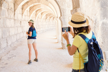 Rear view of young tourist woman with smart phone camera taking pictures of her friend in ancient building