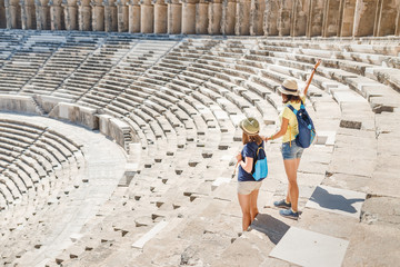 Two young girls student traveler in the ancient amphitheater. archaelolgy travel concept
