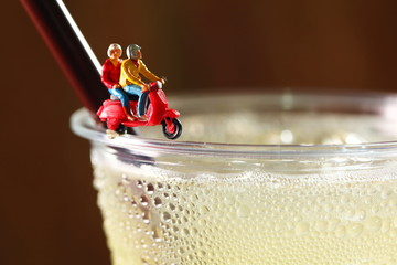 Alcohol drink in plastic cup and miniature plastic figure scene.