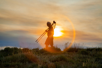 Seasoned Photographer Walks With His Camera On Tripod At Sunset