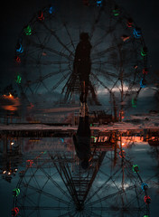A magnificent surreal view of the Ferris wheel and a girl with a reflection at sunset