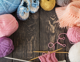 Colorful skeins of yarn and knitted products are handmade on wooden surface