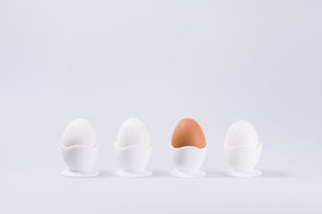three white eggs and one Brown in his egg, isolated on white background with space for text