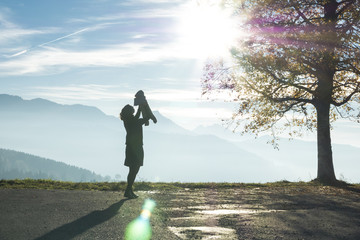 Silhouette of Woman Holding Baby Near the Swiss Alps