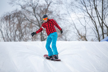 Picture of man wearing helmet riding snowboard from snow slope