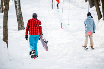 Photo of walking snowboarders from back in winter park