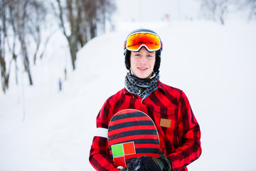 Photo of athlete in helmet with snowboard on blurred background