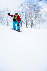 Image of sportsman in helmet with snowboard riding in snowy resort