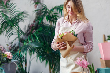 Photo of florist makes bouquet on background of indoor plants