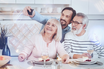 Just smile. Positive delighted adult son takign selfies with his aged parents while sitting together in the kitchen and expressing gladness