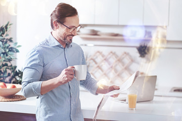 Daily press. Cheerful smiling adult man reading newspaper and drinking coffee while standing in the kitchen