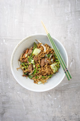 Traditional stir-fried Thai phat mama mie noodles with pork and vegetables as top view in a bowl with copy space