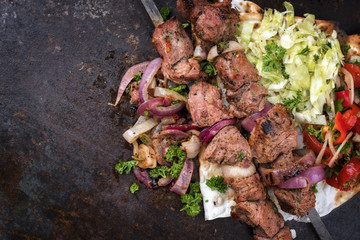 Traditional Greek souvlaki barbecue skewer with cabbage and tomato onion salad as top view on phyllo bread with copy space left