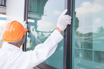 The technician's hands will install aluminum windows.