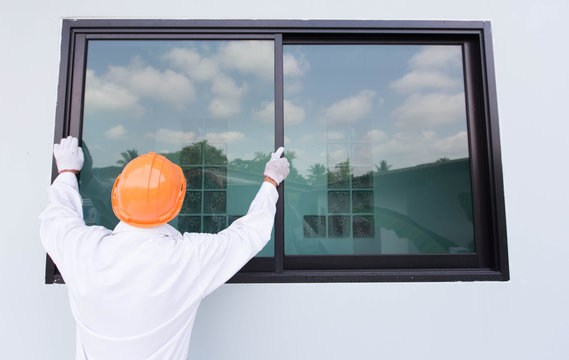 The technician's hands will install aluminum windows.