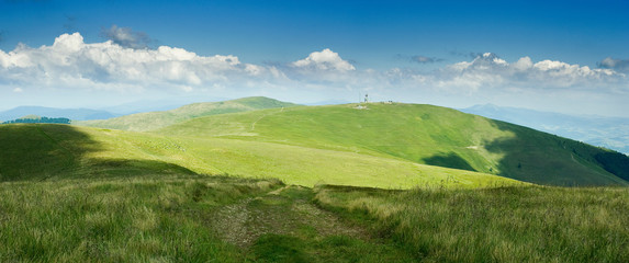 Poster Hill on top of green Carpathian mountains range with blue sky on a sunny day, empty landscape background of wide panorama