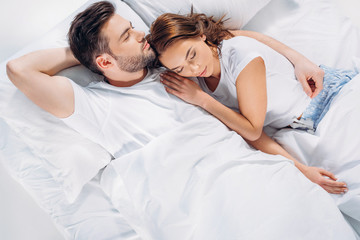 overhead view of young couple sleeping in bed together