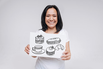 Tasty food. Cheerful emotional young woman smiling and looking glad while being in a popular cafe and ordering delicious tasty cake and tea
