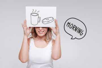 Good morning. Positive young cheerful woman feeling optimistic and having a pleasant morning with tasty breakfast