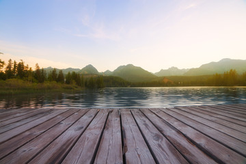 Forest Alpine mountain lake and wooden board background