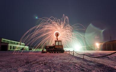 Burning steel wool on the excavator, winter night landscape,