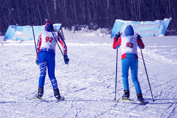 Winter extreme sport of two young skiers on the ski run to the finish line