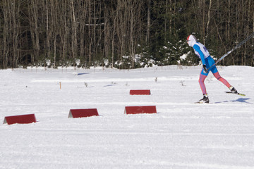 Photo from back of athlete skier in forest at winter .