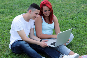 Teenagers on the grassland with digital devices