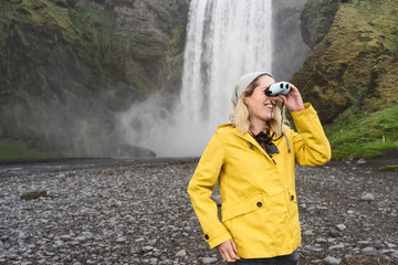 Woman looking through small binoculars with waterfall behind