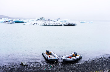 two inflatable ribs by the shore with icebergs