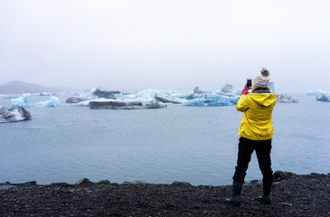 Woman taking a picture on her phone of icebergs in the sea