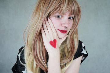 Chica joven y rubia con un corazón pintado en la mano