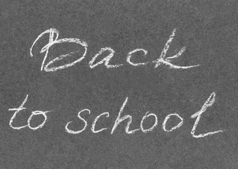 "Hand drawn inscription white pastel crayon ""Back to school"" on the black craft paper. Back to school background with title texts poster design"
