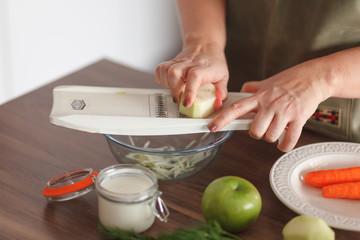 Woman slice kohlrabi in bowl