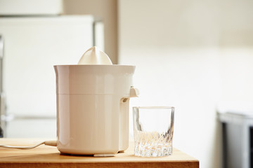 Electric juicer and empty glass in a modern kitchen